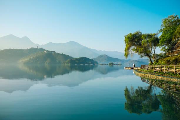 reflexion der bäume, berge und inseln auf dem see von klarem wasser, sonne-mond-see. - insel taiwan stock-fotos und bilder