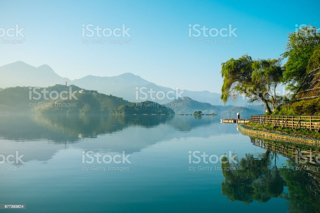 Reflection of trees, mountains, and islands on the clear water lake, sun moon lake. stock photo