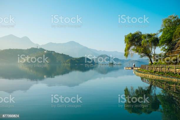 Photo of Reflection of trees, mountains, and islands on the clear water lake, sun moon lake.