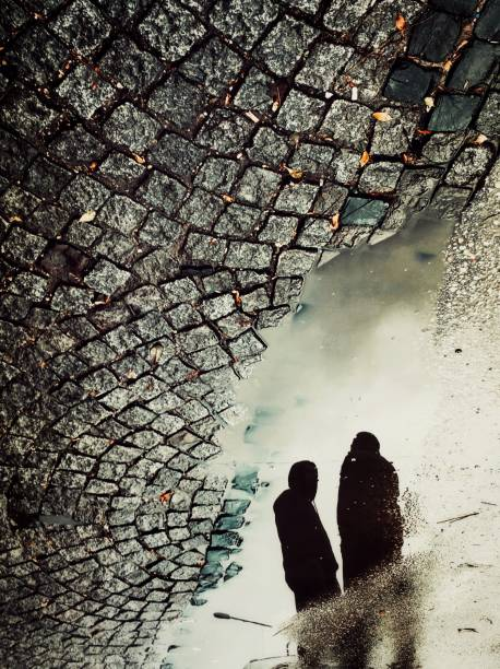Reflection of two men on the puddle