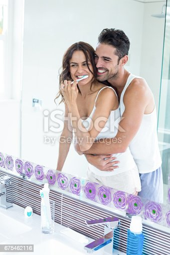 675462768 istock photo Reflection of wife brushing teeth while husband embracing her 675462116