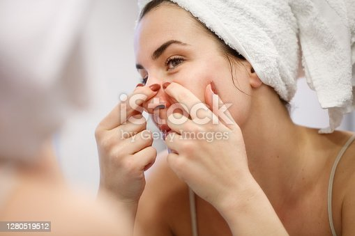 Reflection of woman in bathroom mirror wearing towel on hair after shower, squeezing blackead on her nose side with index fingernails