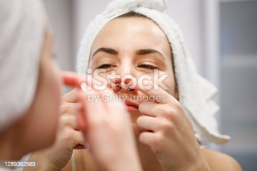 Reflection of woman in bathroom mirror wearing towel on hair after shower, squeezing blackead on her nose with index fingernails