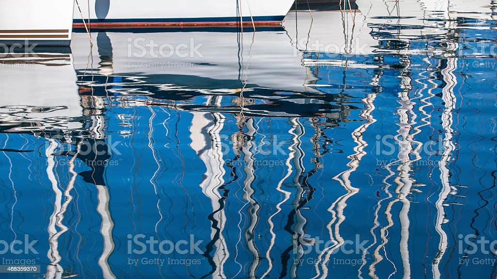 Reflection of yacht masts in the water of the Harbor. royalty-free stock photo