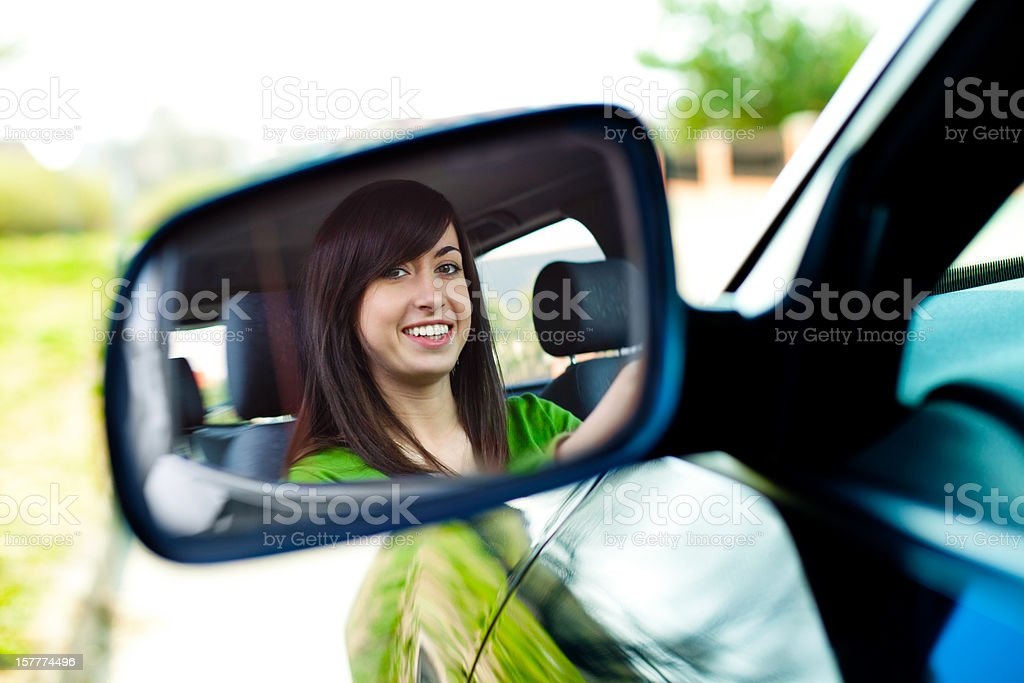 Reflection of young girl in the car mirror royalty-free stock photo