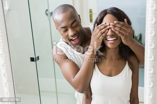 Reflection of young man covering womans eyes in front of mirror