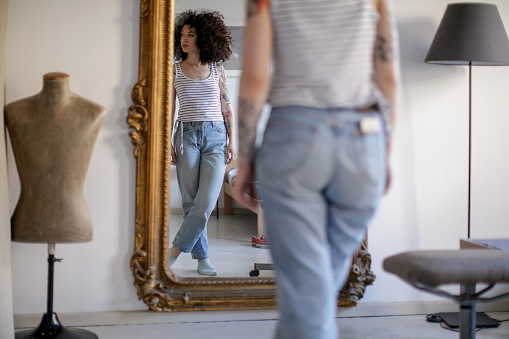 Reflection of a young tattooed woman with brown curly hair standing in front of the mirror and looking away