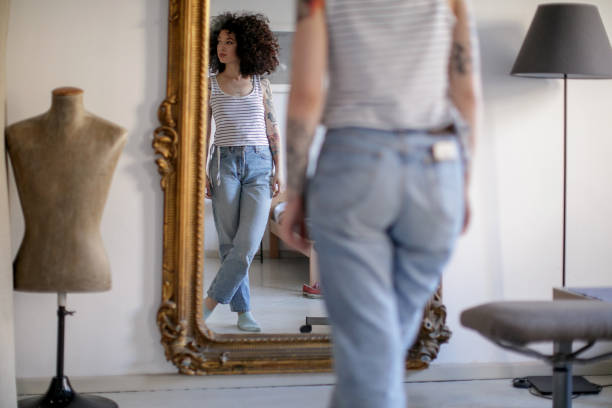 reflection of young tattooed woman in the mirror - woman mirror foto e immagini stock