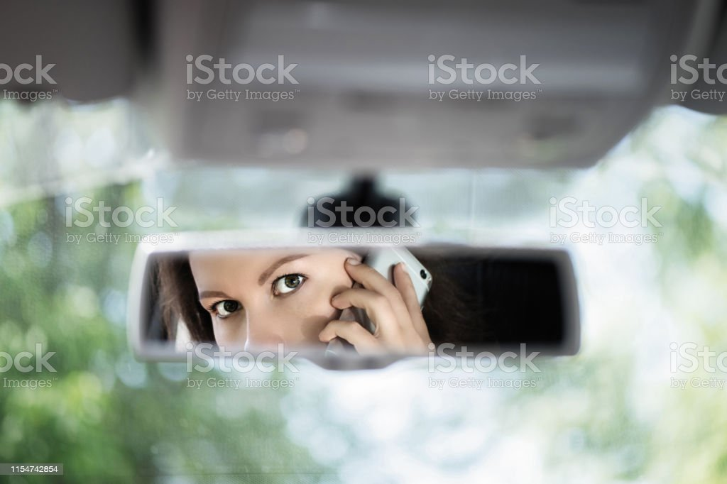 Reflection of young woman talking on a mobile phone in the car rear...