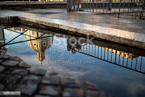 872969580istockphoto Reflection on a puddle of the Saint Peter Basilica and an elderly couple enjoying the view of Rome, Italy. 1089160720