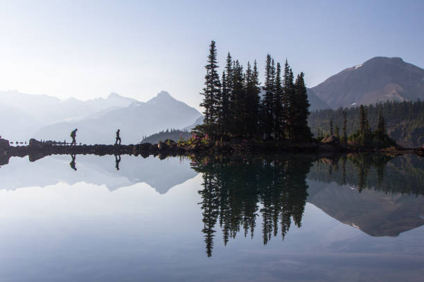 Reflection Hikers reflect in the water at Garibaldi Lake in British Columbia. reflection lake stock pictures, royalty-free photos & images