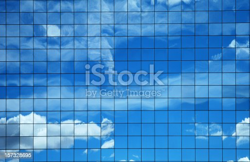 Sky and clouds reflected in a modern building glass facade.