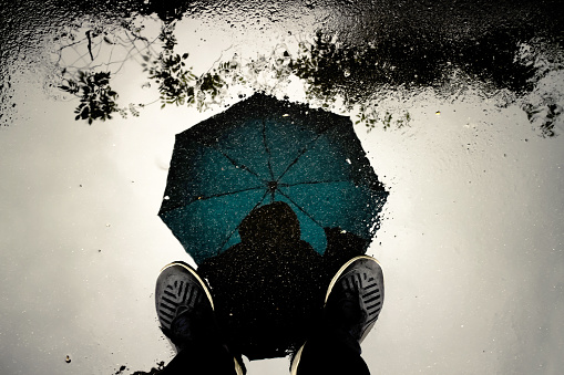 istock Reflection shadow man and umbrella walking in the rain. 939910642