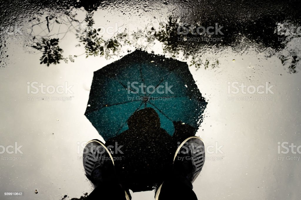 Reflection shadow man and umbrella walking in the rain. stock photo