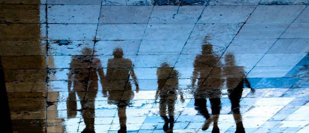 Reflection shadow silhouette on wet city sidewalk of mysterious people walking away the night