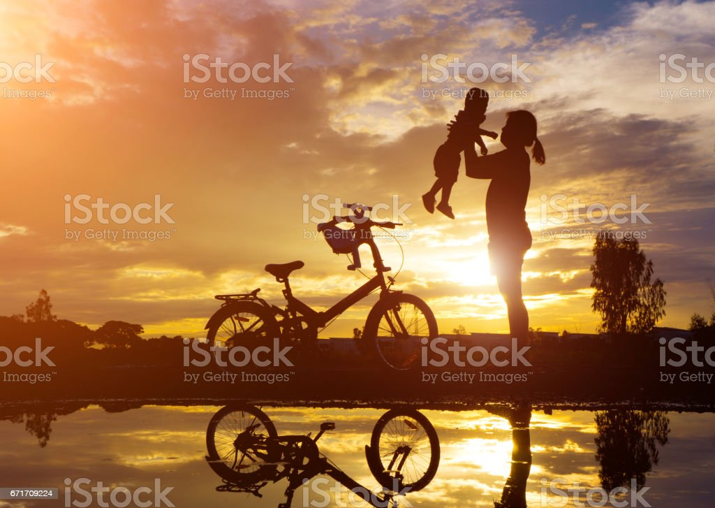 Reflection Silhouette of mother with her toddler against the sunset. stock photo