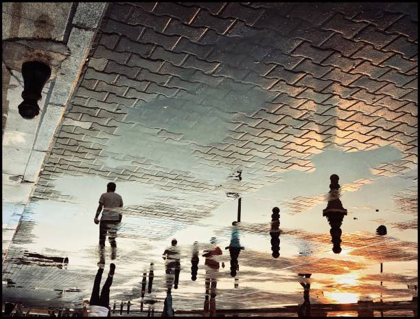 Reflection view of people walking after rain on the street at sunset
