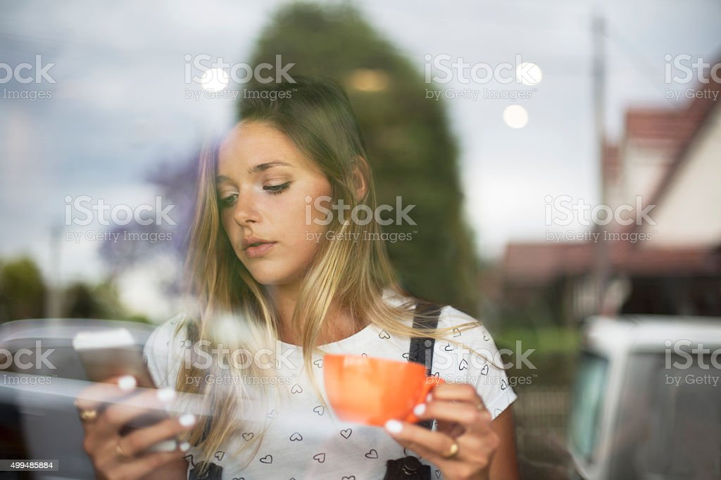 Young woman having coffee break, reading phone text in coffee bar,...