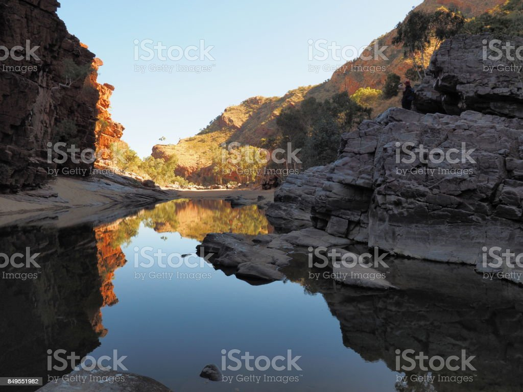 Reflections in the dark waters of Ormiston Gorge with red glowing cliffs stock photo