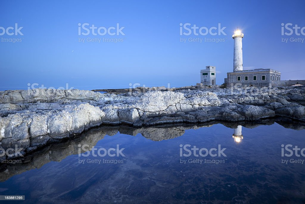 Reflections of a lighthouse at dusk on Sicily, Italy royalty-free stock photo