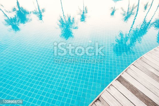 Reflections of palm trees in the blue water of a swimming pool