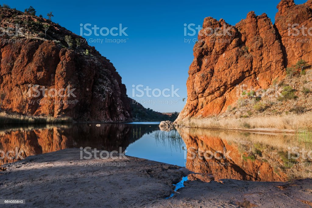Reflections of rock formations at Glen Helen Gorge water hole stock photo
