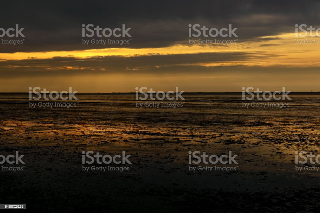 Reflections of sunset in low tide beach stock photo