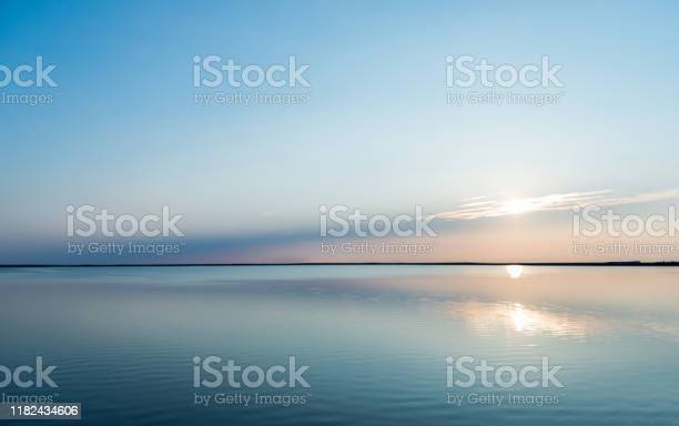 Photo of Reflections of sunset with cloudscape in lake water