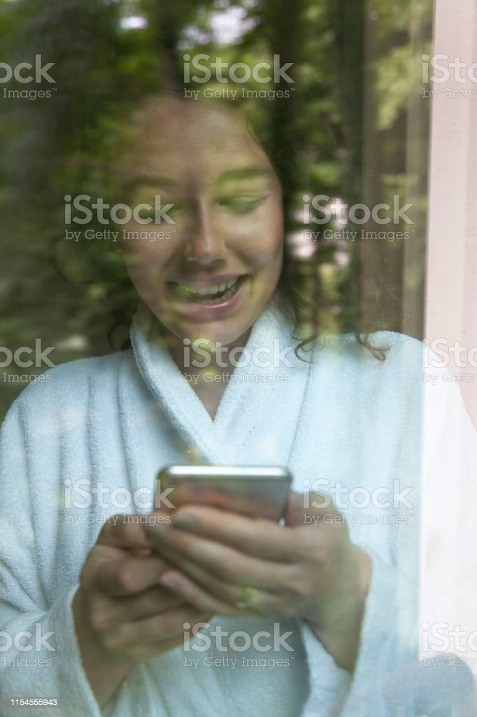 Young woman using a smart phone while front on the window