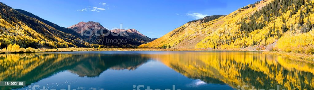 Reflective Crystal Lake with yellow mountains under blue sky stock photo