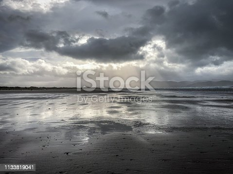 Moody Shot of a Beach at Low Tide on a Cloudy, Stormy Day - with Reflective Sheets of Water Below and Rays of Sun Shining Through the Clouds Above