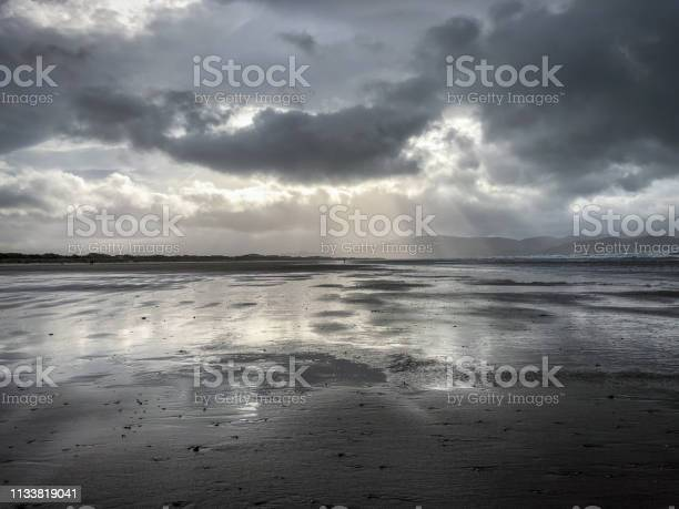 Photo of Reflective Water on a Beach at Low Tide on an Overcast Day