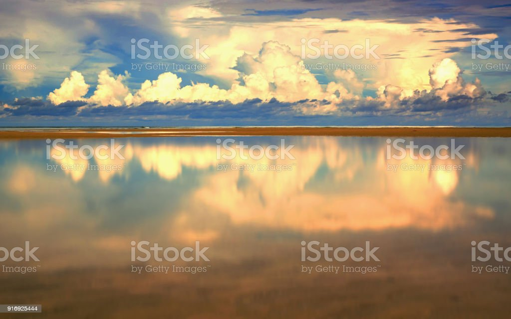 Refletion of suset sky on water surface at beatiful beach stock photo
