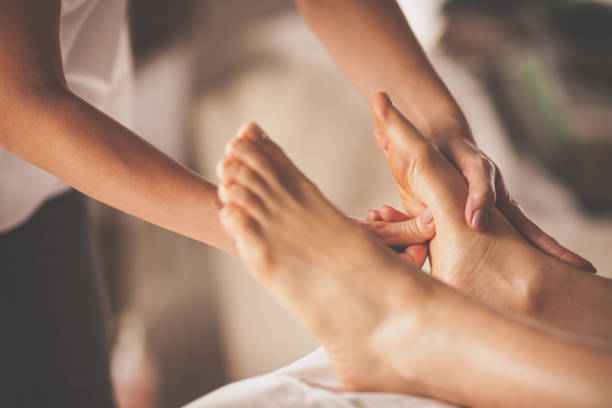 Reflexologist applying pressure to foot with thumbs stock photo