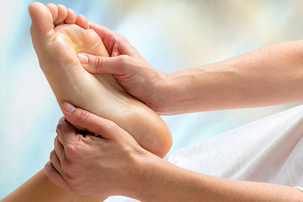 reflexologist doing treatment on foot. - podiatry stock pictures, royalty-free photos & images