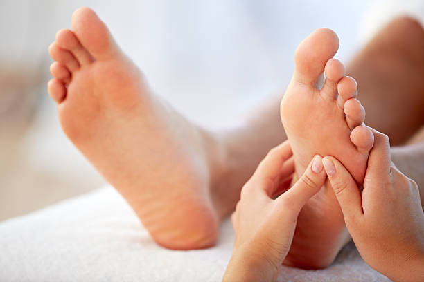 Reflexology foot massage Close-up of hands of massage therapist giving a foot massage foot massage stock pictures, royalty-free photos & images