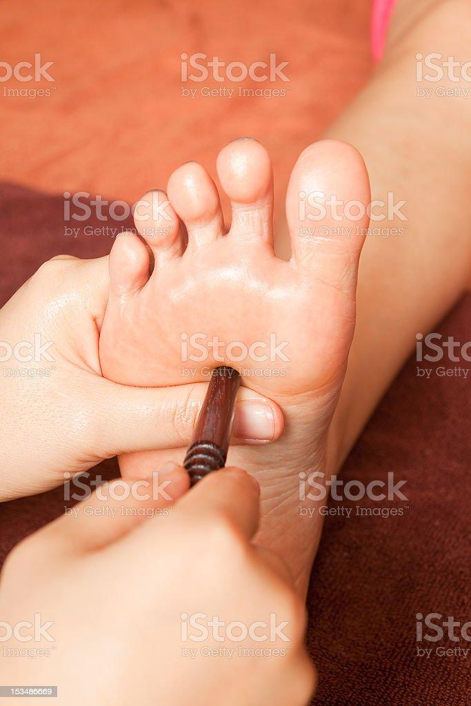 reflexology foot massage, spa treatment by wood stick royalty-free stock photo