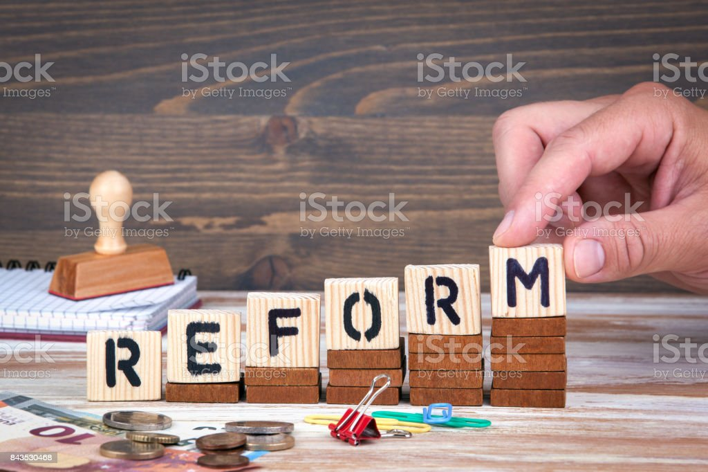 Reform concept. Wooden letters on the office desk, informative and communication background stock photo