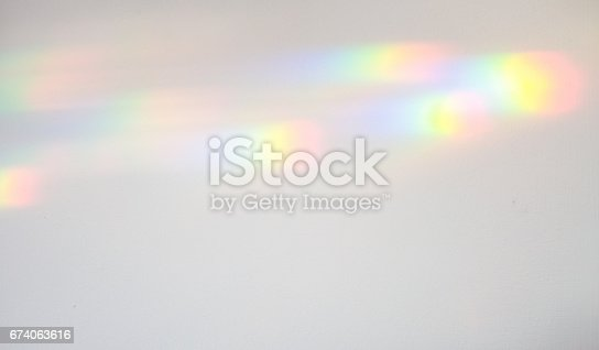 Refracted light falling on a wall, and creating spectrum patterns of colour.