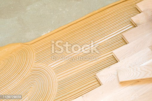 Close-up of a fresh layer of glue and hardwood planks during the parquet floor installation.