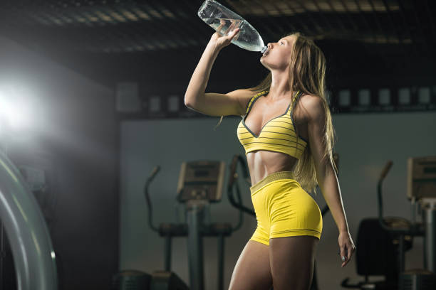 Refreshing after a workout. Beautiful woman drinking water in gym stock photo