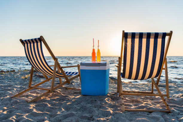 refreshing beverages on cooler and chaise lounges on sandy beach at sunset refreshing beverages on cooler and chaise lounges on sandy beach at sunset cooler container stock pictures, royalty-free photos & images