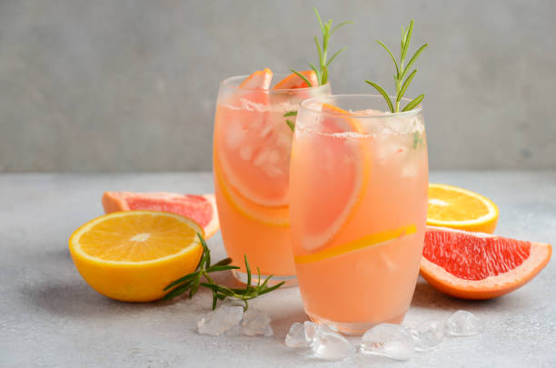 refreshing citrus cocktail with grapefruit, orange and rosemary - grapefruit cocktail stock photos and pictures