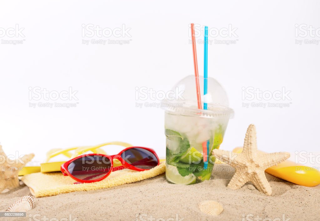 Refreshing cocktail with mint, lime and ice on the sand with beach items close up ロイヤリティフリーストックフォト