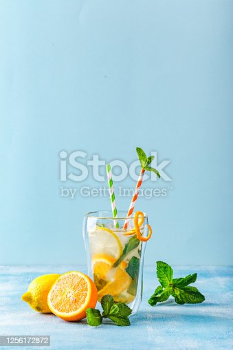 Summer refreshing cocktails, lemonade or mojito with lemon, orange and mint with ice in a glass cup and with a striped paper straw. On a light blue background. Copy space.