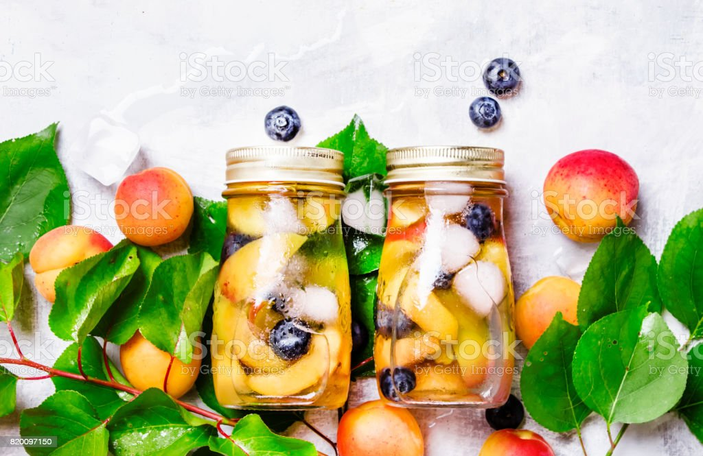 Refreshing cold drink with apricot, blueberry and ice