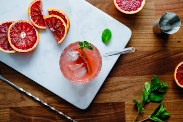 Refreshing cold summer cocktail with blood orange and mint on a marble tray. Top view, flat lay composition. stock photo