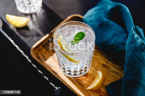 Refreshing cold summer cocktail with soda water, lemon and ice cubes on a wooden tray.