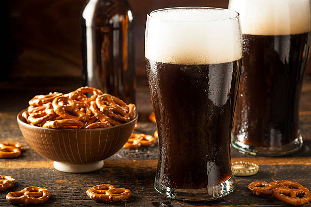 refreshing dark stout beer - dark beer stock photos and pictures