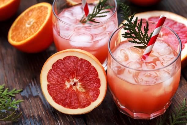 boisson rafraîchissante, cocktail de pamplemousse. cocktail detox avec des fruits frais - infusion pamplemousse photos et images de collection
